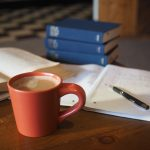 cup of coffee with notebook, pen and stack of books
